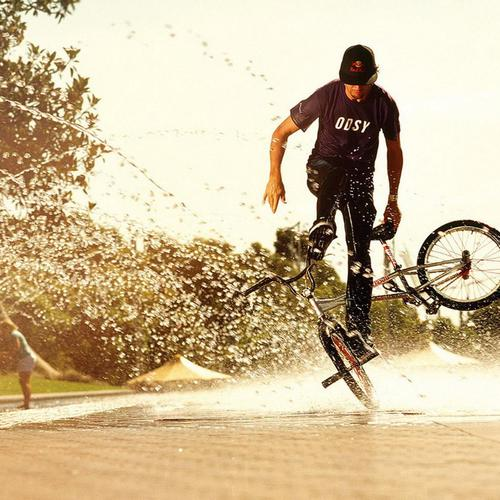 A guy playing with bike in water