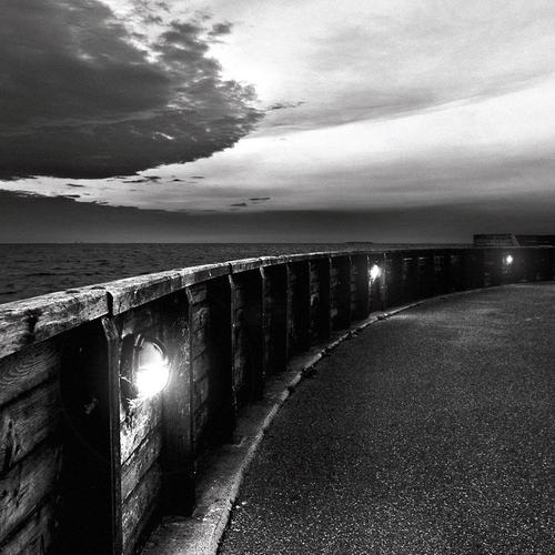 Black and white clouds on seacoast road wallpaper