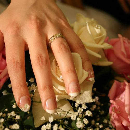 Bride hand with wedding ring and flowers