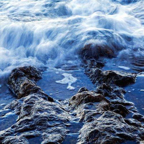 Close up of surf on a rocky beach