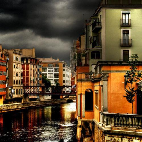 Colorful buildings on a canal in a storm wallpaper