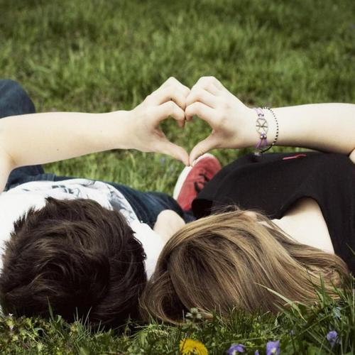 Couple lying on the grass making heart shape