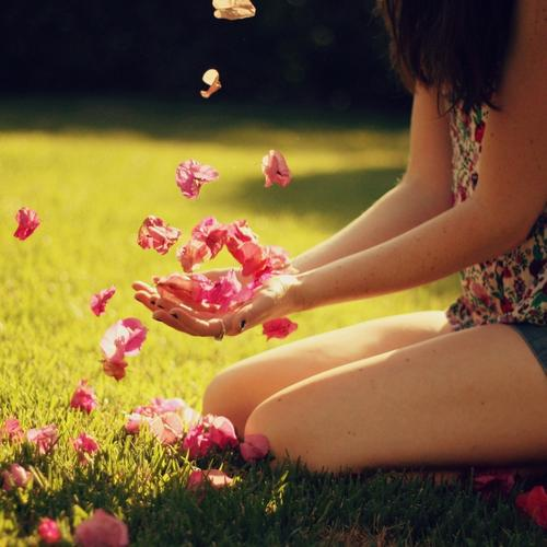 Girl is playing with flower petal