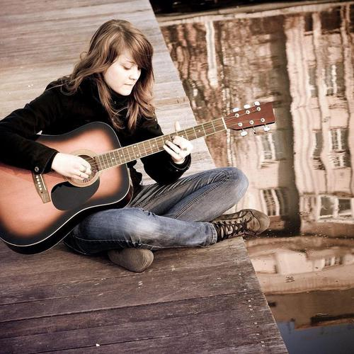 Girl playing guitar on the dock