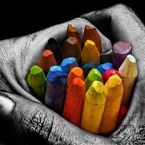 Hands holding colorful crayons