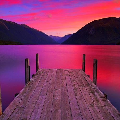 Jetty on lake in red sunset wallpaper