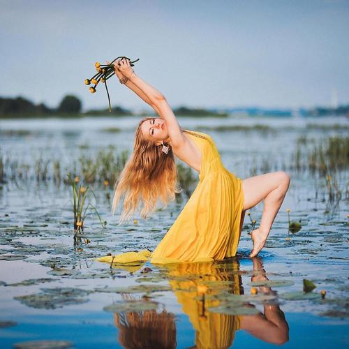 Lady in yellow dress dancing in pond