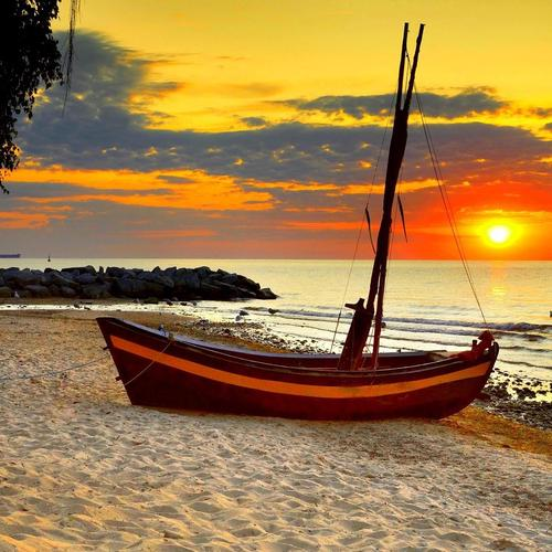 Little sailboat on a beach at sunset wallpaper