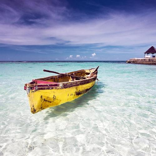 Lonely boat floating on crystal clear Caribbean sea
