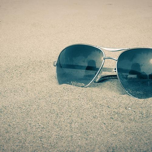 Macro of sunglasses on the beach sands