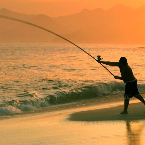 Man fishing on the beach in sunset
