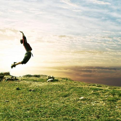 Man jump up from the green grass in sunlight
