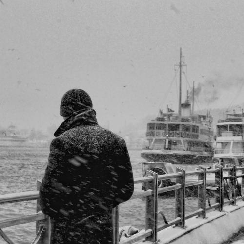 Man standing on harbor in winter