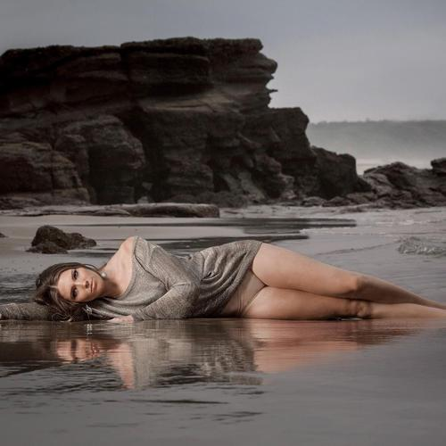 Model lying In the wet sand