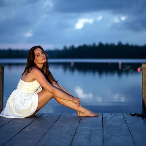 Pretty girl in white dress on dock at dusk