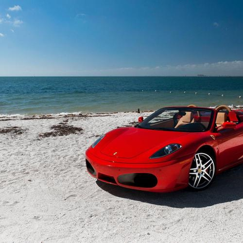 Red ferrari on the beach