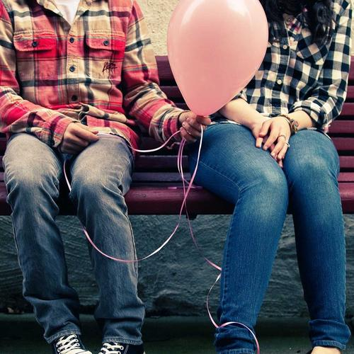Romantic in love couple sitting on bench with pink balloon