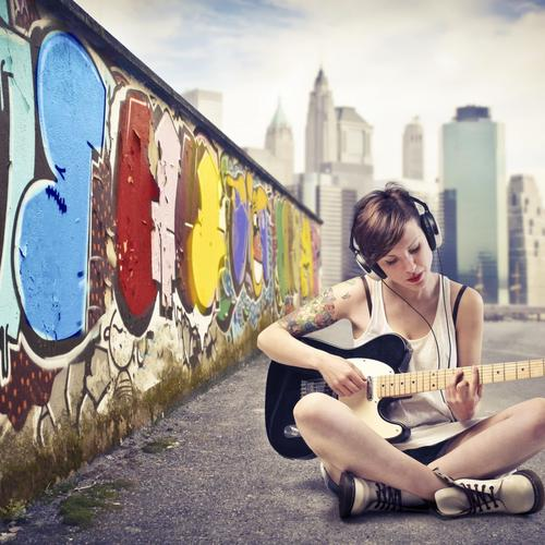 Short hair girl playing guitar nearby graffiti wall wallpaper