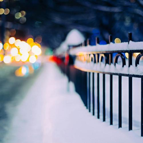 Snowy fence in winter city night wallpaper