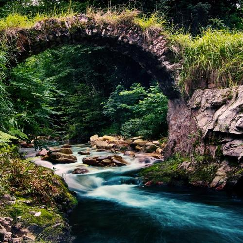 Stone arch over stream wallpaper