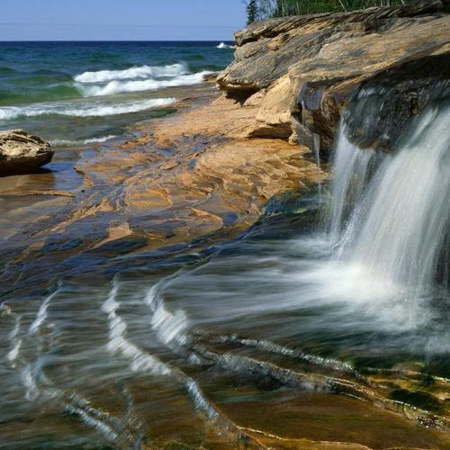 Waterfall on beach wallpaper