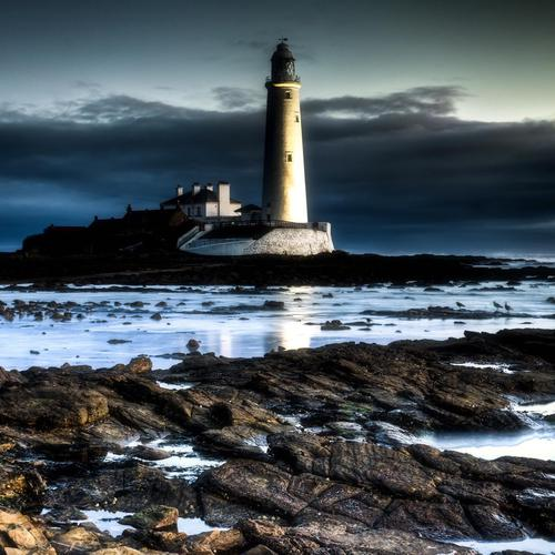 Wonderful lighthouse on a rocky shore wallpaper